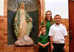 Three students standing next to Virgin Mary statue.