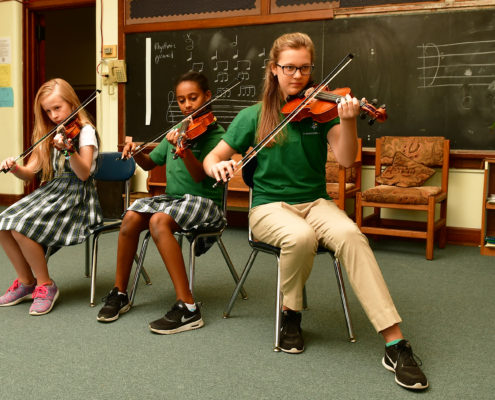 Three girls playing violins in front of class.