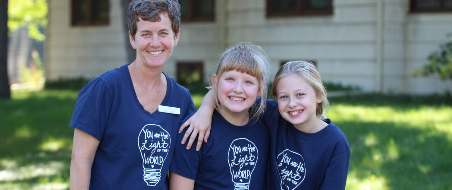 St Peters staff and two girls smiling together