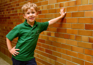 Boy student standing with his hand on brick wall.