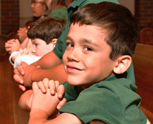 Boy student praying with other students in class.