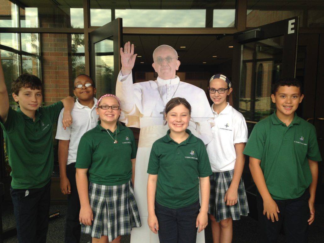 Students standing with a life-size cutout of the pope.